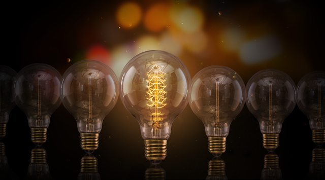 Vintage Edison light bulbs on dark background with empty space for text.